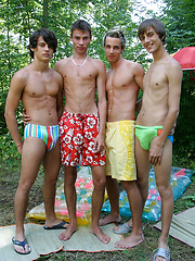These four tanned twinks have found a quiet corner in the bushes and are busy sucking cock